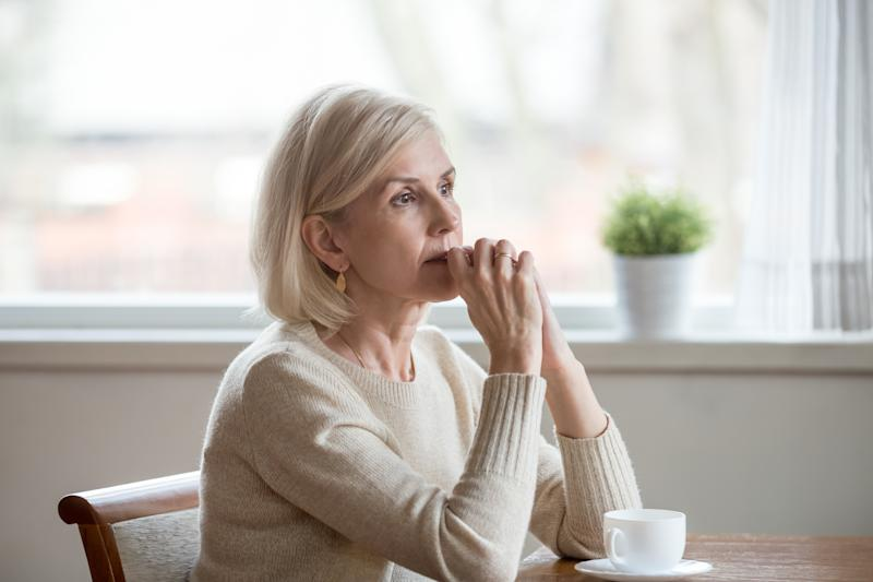 Woman spend time at home alone sitting at table with cup of tea folds hands on chin lost in thoughts. Old lonely female has health problem or thinking about life, reminiscing the past relive memories