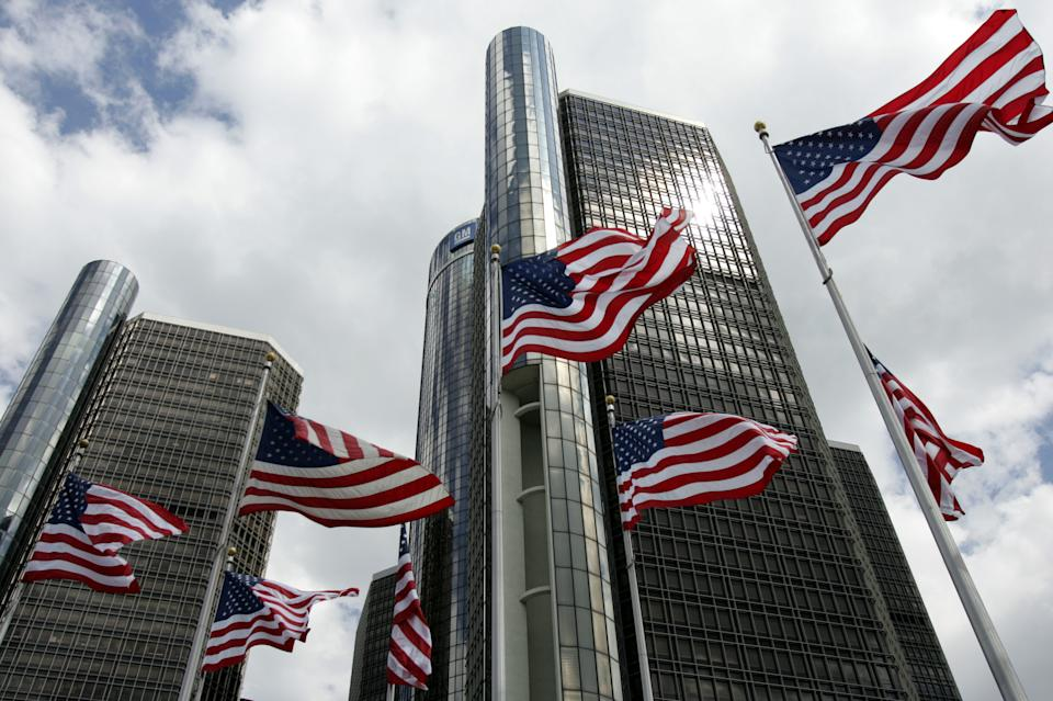 American flags fly in front of General Motors Corp. world headquarters in downtown Detroit, Michigan, July 1, 2005. Big consumer incentives delivered blockbuster results for the world's largest automaker in June, with its U.S. sales jumping 41 percent over the same month last year. REUTERS/Rebecca Cook  RC/KS