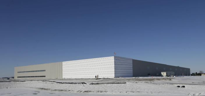 This Dec. 9, 2013 photo shows workers outside the Brownells, Inc. distribution and retail facility under construction along Interstate 80, in Grinnell, Iowa. The central Iowa city of 9,100 is home to Grinnell College, the selective liberal arts institution known for its commitment to social justice. Billed as the world's largest supplier of firearms accessories, Brownells is a family-owned company that has long been based 20 miles south of Grinnell in Montezuma, Iowa. (AP Photo/Charlie Neibergall)