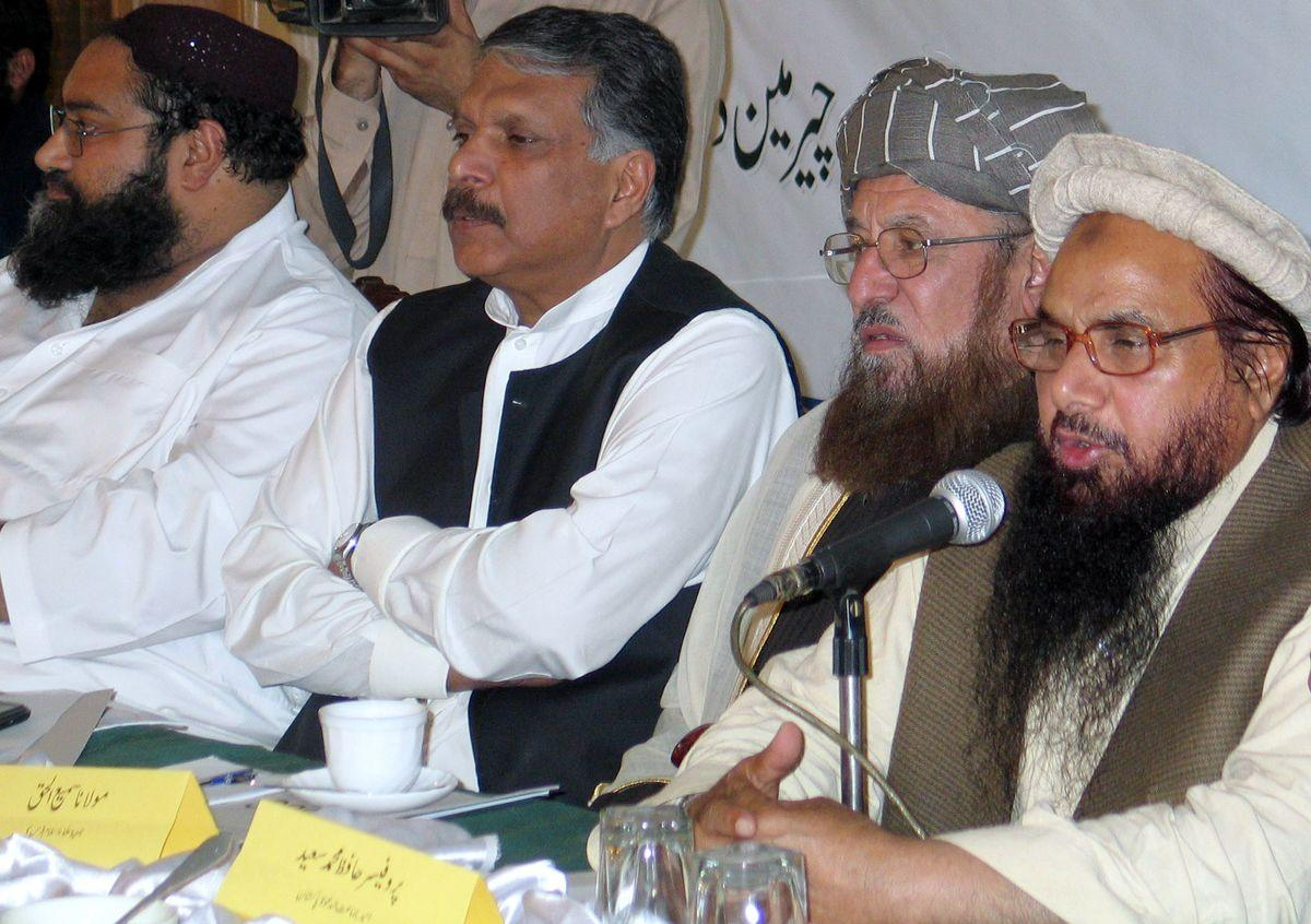 Hafiz Muhammad Saeed, right, speaks during a news conference called by an alliance of Pakistani religious parties, the Defense of Pakistan Council, in Peshawar on March 19, 2012.