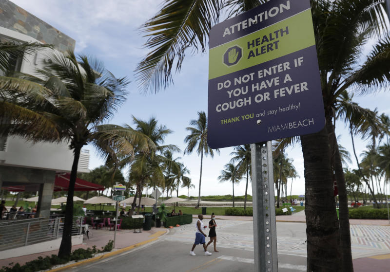 FILE - In this June 22, 2020, file photo a couple walks past a sign asking people not to visit Miami Beach, Florida's famed South Beach if they have a cough or fever. An Associated Press analysis of coronavirus case data shows the virus has moved, and is spreading quickly, into Republican areas, a new path with broad potential political ramifications. (AP Photo/Wilfredo Lee, File)