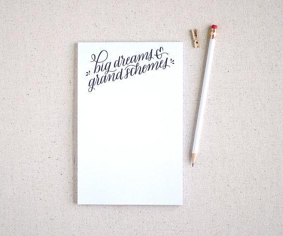 """Big Dreams & Grand Schemes Notepad; $10 at <a href=""""https://www.etsy.com/listing/170966489/hand-lettered-recycled-notepad-to-do?ref=sr_gallery_14&ga_search_query=notepad&ga_page=10&ga_search_type=all&ga_view_type=gallery"""" rel=""""nofollow noopener"""" target=""""_blank"""" data-ylk=""""slk:etsy.com"""" class=""""link rapid-noclick-resp""""><em>etsy.com</em></a>"""