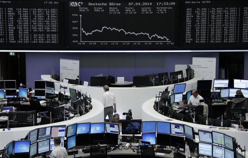 Traders are pictured at their desks in front of the DAX board at the Frankfurt stock exchange April 7, 2014. REUTERS/Remote/Stringer