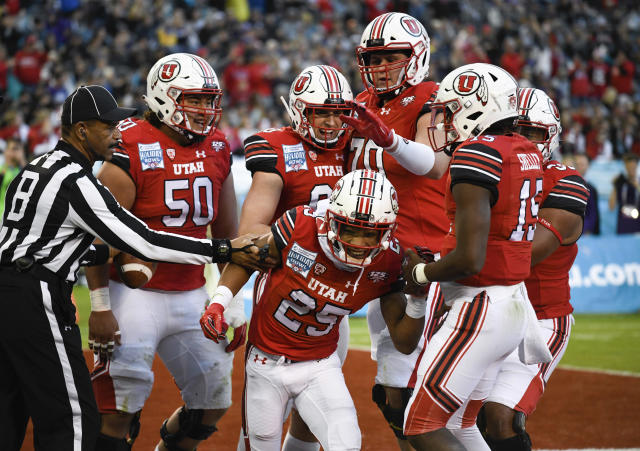 Utah players congratulate wide receiver Jaylen Dixon (25) after scoring a touchdown during the first half of the Holiday Bowl NCAA college football game against Northwestern, Monday, Dec. 31, 2018, in San Diego. (AP Photo/Denis Poroy)
