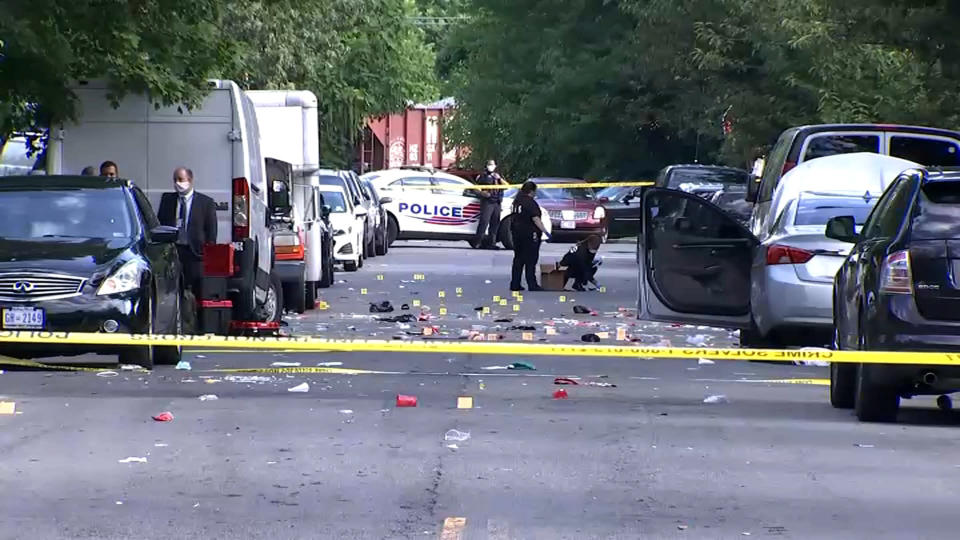In this image from video provided by NBC4 Washington, law enforcement work the scene of a shooting, Sunday, Aug. 9, 2020, in Southeast Washington. (NBC4 Washington via AP)