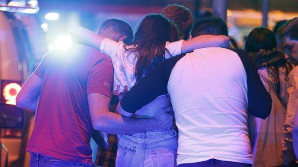 PHOTO: People help an injured woman walk near the Manchester Arena after reports of an explosion on May 22, 2017 in Manchester, England. (Goodman/LNP/REX/Shutterstock)