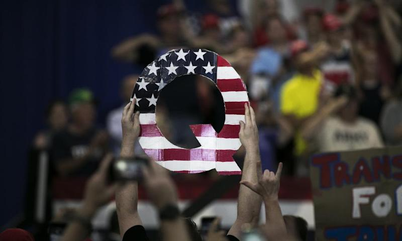 A man holding a cutout letter Q decorated with the stars and stripes