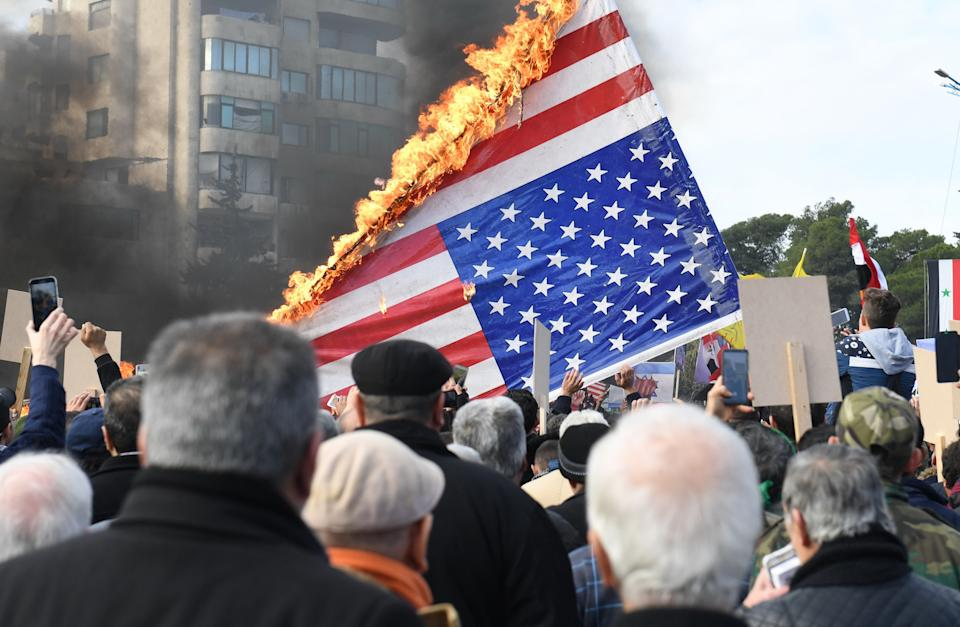 Syrian demonstrators burn the US flag as they gather in the central Saadallah al-Jabiri square in the northern Syrian city of Aleppo on January 7, 2020, to mourn and condemn the death of Iranian military commander Qasem Soleimani, and nine others in a US air strike in Baghdad. (Photo by - / AFP) (Photo by -/AFP via Getty Images)