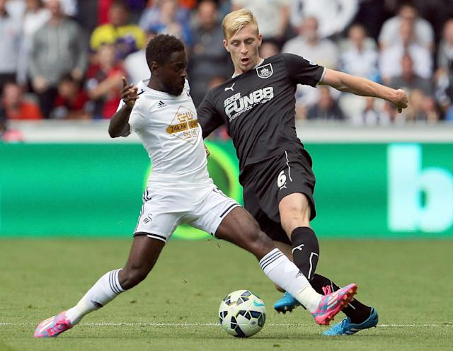 Swansea City's English midfielder Nathan Dyer (L) tackles Burnley's English defender Ben Mee (R) during the English Premier League football match between Swansea City and Burnley at the Liberty Stadium in Swansea on August 23, 2014 (AFP Photo/Geoff Caddick)