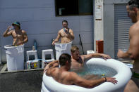 Members of Australia's men's rugby sevens team soak in ice baths following practice in the midday heat at the Tokyo 2020 Olympics, in Tokyo, Friday, July 23, 2021. (AP Photo/David Goldman)