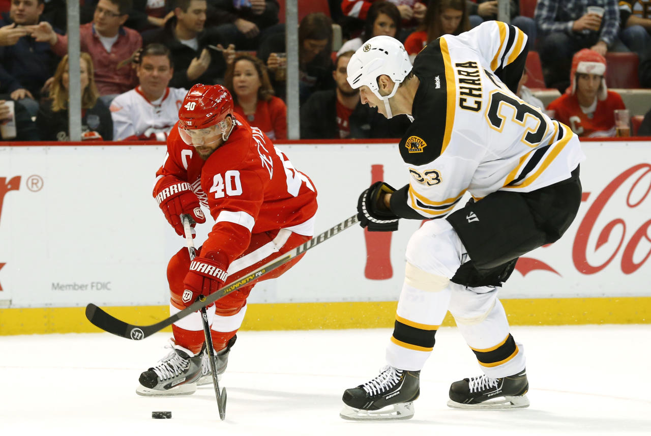Detroit Red Wings left wing Henrik Zetterberg (40), of Sweden, and Boston Bruins defenseman Zdeno Chara (33), of the Czech Republic, battle for the puck in the second period of an NHL hockey game in Detroit Wednesday, Nov. 27, 2013. (AP Photo/Paul Sancya)