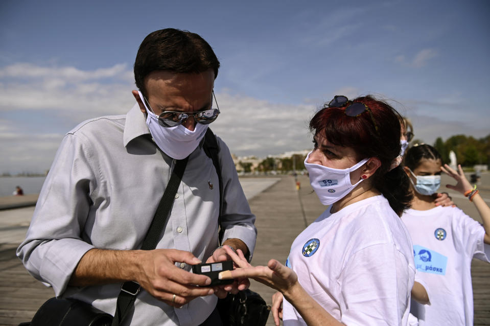 A participant has her oxygen saturation measured, during an event organized by the local medical association, in order to support the use of protective masks, in the northern city of Thessaloniki, Greece, Saturday, Oct. 3, 2020. Lung doctors staged a public demonstration of the benefits of face masks by fast-walking a distance of 2 kilometers (1.25 miles) through the city center aiming to debunk a widely-circulated rumor by anti-mask conspiracy theorists that wearing one left people short of breath. (AP Photo/Giannis Papanikos)