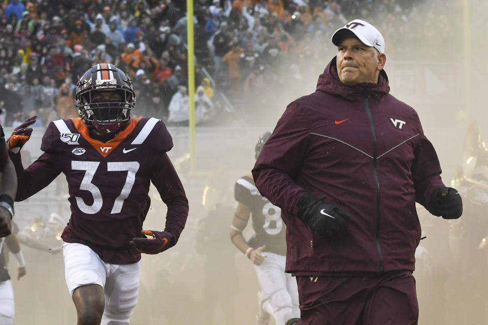 BLACKSBURG, VA - NOVEMBER 23: Head coach Justin Fuente of the Virginia Tech Hokies and defensive back Brion Murray #37 of the Virginia Tech Hokies run onto the field prior to the game against the Pittsburgh Panthers at Lane Stadium on November 23, 2019 in Blacksburg, Virginia. (Photo by Michael Shroyer/Getty Images)