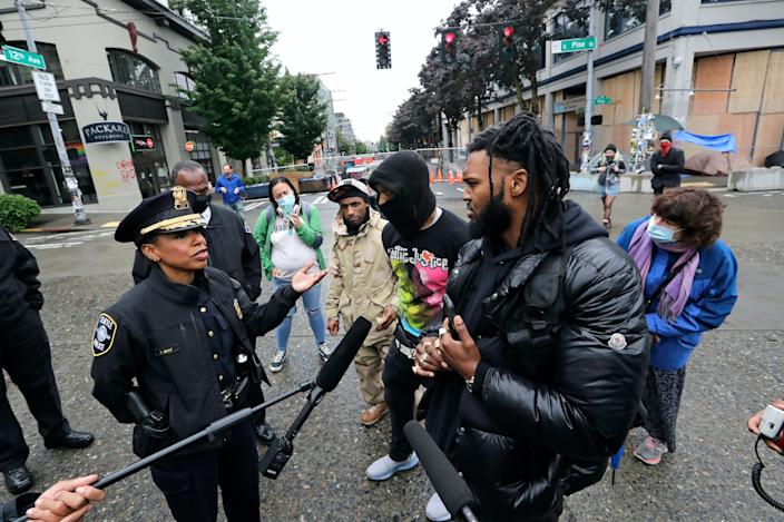 """Seattle Police Chief Carmen Best, left, talks to an activist on June 9, 2020. Best resigned from the police in early September. <p class=""""copyright""""><a href=""""https://newsroom.ap.org/detail/AmericaProtestsSeattle/1eaf7d816bb044d298385ee264a7188e/photo?Query=black%20police%20officer%20protest&mediaType=photo&sortBy=arrivaldatetime:desc&dateRange=Anytime&totalCount=5341&currentItemNo=98"""" rel=""""nofollow noopener"""" target=""""_blank"""" data-ylk=""""slk:Elaine Thompson/AP"""" class=""""link rapid-noclick-resp"""">Elaine Thompson/AP</a></p>"""