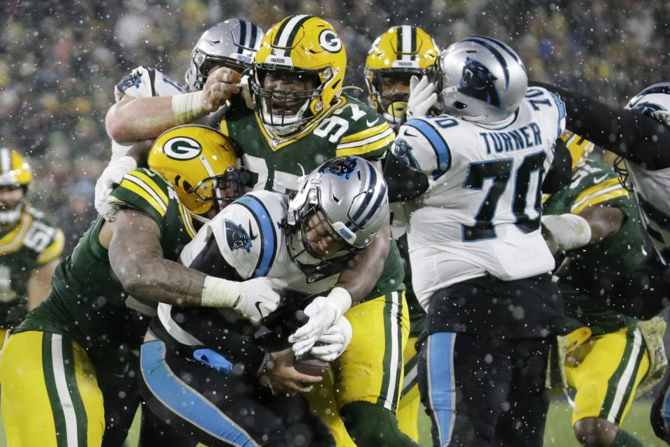 Carolina Panthers' Kyle Allen is sacked by Green Bay Packers' Kenny Clark and Preston Smith during the second half of an NFL football game Sunday, Nov. 10, 2019, in Green Bay, Wis. (AP Photo/Mike Roemer)