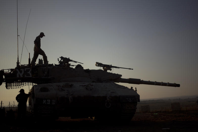 Israeli soldiers work on their tank near the border with Syria on the Golan Heights Tuesday, July 16, 2013. The Israeli military says fire from fighting in neighboring Syria has hit the Israeli-controlled Golan Heights.(AP Photo/Ariel Schalit)