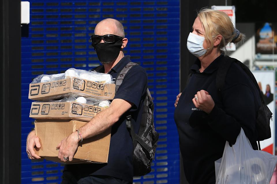 Pedestrians wearing a face mask or covering due to the COVID-19 pandemic, carry boxes and shopping bags as they walk past shops in Oldham, Greater Manchester, northwest England on August 20, 2020. - Oldham, as of Thursday, has one of the highest rates of new COVID-19 infections, and could be subject to a imposed Local Lockdown to prevent the spread of the novel coronavirus. (Photo by Lindsey Parnaby / AFP) (Photo by LINDSEY PARNABY/AFP via Getty Images)