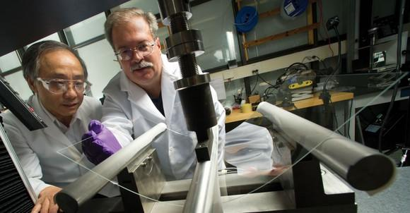 Two Corning scientists looking a pane of bending glass