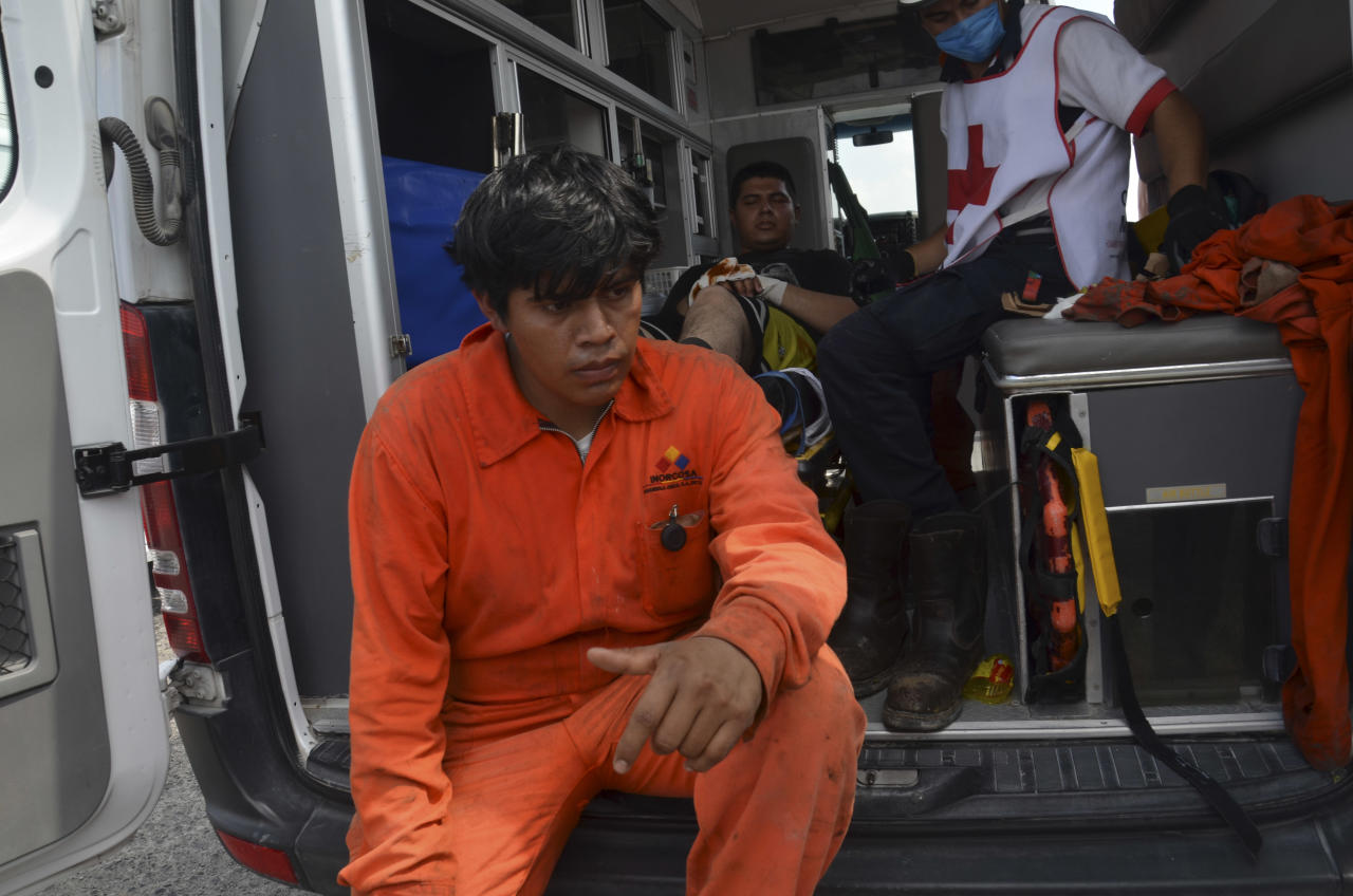 A worker waits to be treated by first responders after an explosion ripped through a gas pipeline distribution center in Reynosa, Mexico near Mexico's border with the United States, Tuesday Sept. 18, 2012. (AP Photo/El Manana de Reynosa)