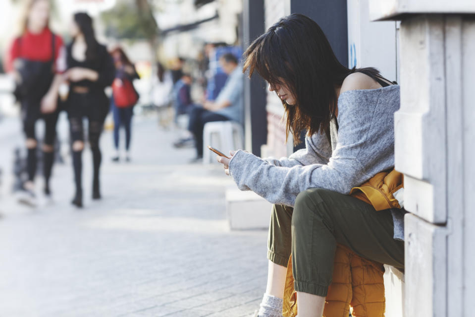 Young woman sitting on near street door and uses smartphone. Hipster girl looking on screen of phone,blogging,chatting,browsing internet. Online marketing, education, distance work. Social network.