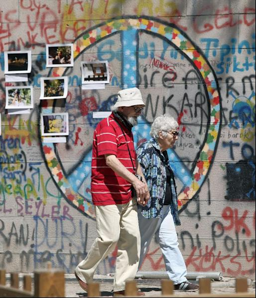 A couple walk past by photographs and graffiti painted by protesters in Kugulu Park in Ankara, Turkey, Wednesday, June 26, 2013. Turkish police on Tuesday detained at least 20 people allegedly involved in violent protests, as Prime Minister Recep Tayyip Erdogan continued to lash out at protesters and a BBC journalist he claimed were part of a conspiracy to harm Turkey. Erdogan reiterated that the protests were orchestrated by forces wanting to prevent Turkey's rise.(AP Photo/Burhan Ozbilici)