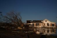 A destroyed home is reflected in flood waters in the aftermath of Hurricane Delta in Creole, Louisiana