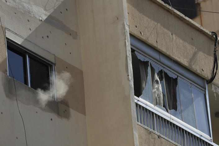 Smoke from a sniper's bullet rises targeting a Christian's house, after deadly clashes erupted along a former 1975-90 civil war front-line between Muslim Shiite and Christian areas, in Ain el-Remaneh neighborhood, Beirut, Lebanon, Thursday, Oct. 14, 2021. Lebanon's interior minister said at least five people have been killed in armed clashes in Beirut that erupted Thursday during protests against the lead investigator into last year's massive blast at the city's port. (AP Photo/Hussein Malla)