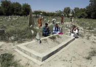 Abdul Rauf right, prays over the grave of his daughter Shahnaz Raufi, a worker at a TV station who was killed in a March attack claimed by the Islamic State group, in Jalalabad, Afghanistan, Wednesday, April 21, 2021. IS has resumed a campaign of targeted killings of minority Shiite Muslims, many of them ethnic Hazaras, as well as women's rights activists and media workers. (AP Photo/Rahmat Gul)