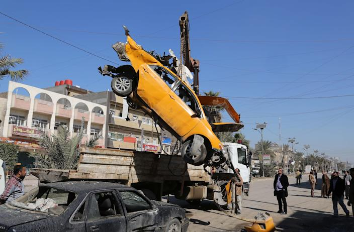FILE - In this Thursday, Feb. 6, 2014 file photo, A wrecked car is removed from the site of a car bomb attack in the Shaab neighborhood of Baghdad, Iraq. Car bombs are one of the deadliest weapons used by the al-Qaida breakaway group in Iraq that dominates the Sunni insurgency in Iraq, with coordinated waves of explosions regularly leaving scores dead in Baghdad and elsewhere across the country. (AP Photo/Karim Kadim, File)