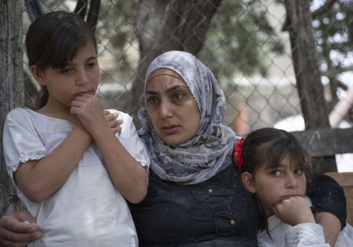 Somaya, the wife of Palestinian Osama Mansour, who was shot to death by Israeli soldiers at a temporary checkpoint in the occupied West Bank earlier this month, holds their 10 year-old twins Nissan, left and Bissan, right, at their family house, in the West Bank village of Biddu, west of Ramallah, Tuesday, April 20, 2021. Somaya, who was in the car with her husband and was wounded by the gunfire, says they followed the soldiers' instructions and posed no threat. The shooting death has revived criticism of the Israeli military's use of deadly force. (AP Photo/Nasser Nasser)