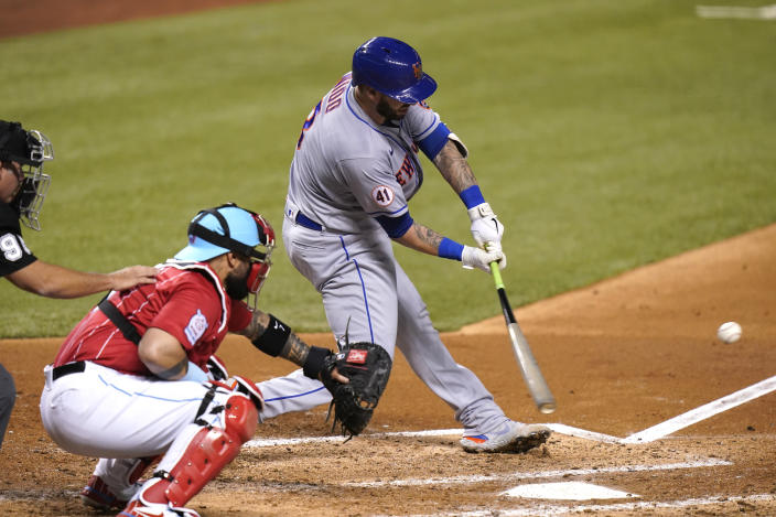 New York Mets' Tomas Nido hits a double to score Dominic Smith during the fourth inning of a baseball game against the Miami Marlins, Friday, May 21, 2021, in Miami. At left is Marlins catcher Sandy Leon. (AP Photo/Lynne Sladky)