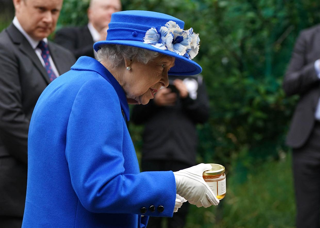 Britain's Queen Elizabeth II receives a gift of a jar of honey during a visit to The Childrens Wood Project in Glasgow on June 30, 2021, as part of her traditional trip to Scotland for Holyrood Week. (Photo by Andrew Milligan / POOL / AFP) (Photo by ANDREW MILLIGAN/POOL/AFP via Getty Images)