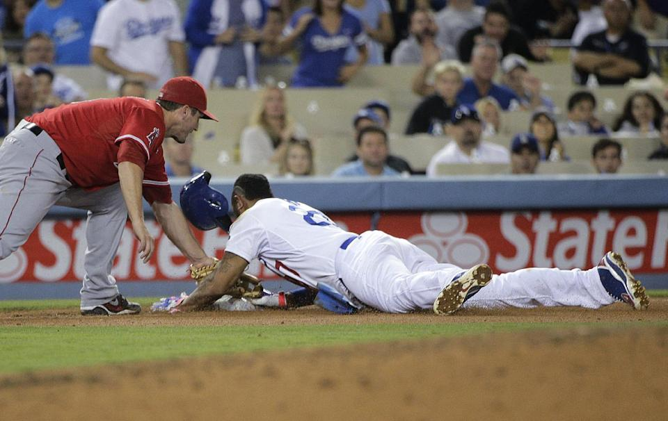 Los Angeles Dodgers' Matt Kemp safely takes third base as Los Angeles Angels third baseman David Freese applies a late tag, following a throwing error as Kemp stole second during the sixth inning of a baseball game on Tuesday, Aug. 5, 2014, in Los Angeles. (AP Photo/Jae C. Hong)