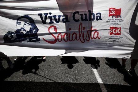 People hold a banner with an image of Cuba's former President Castro as they take part in a march marking the 62nd anniversary of the July 26, 1953 rebel assault on the Moncada military barracks in central Madrid