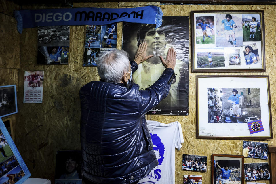 A man touches a poster of soccer legend Diego Maradona, in Naples, Italy, Wednesday, Nov. 25, 2020. Diego Maradona has died. The Argentine soccer great was among the best players ever and who led his country to the 1986 World Cup title before later struggling with cocaine use and obesity. He was 60. (Alessandro Garofalo/LaPresse via AP)