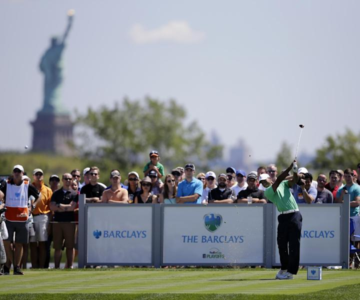 Tiger Woods hits a tee shot on the third hole during the third round of The Barclays golf tournament Saturday, Aug. 24, 2013, in Jersey City, N.J. The Statue of Liberty is seen in the background left. (AP Photo/Mel Evans)