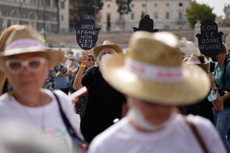 """Women hold banners reading """"Afghan sisters you're not alone"""" and """"with the Afghan women"""" during a demonstration in favor of Afghan women's rights, staged by women rights activists, in Rome, Saturday, Sept. 25, 2021. (AP Photo/Andrew Medichini)"""