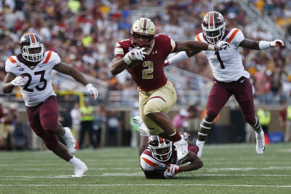 Boston College running back AJ Dillon (2) breaks tackle on Virginia Tech defensive back Jermaine Waller, bottom, on a touchdown run during the first half of an NCAA college football game in Boston, Saturday, Aug. 31, 2019. (AP Photo/Michael Dwyer)