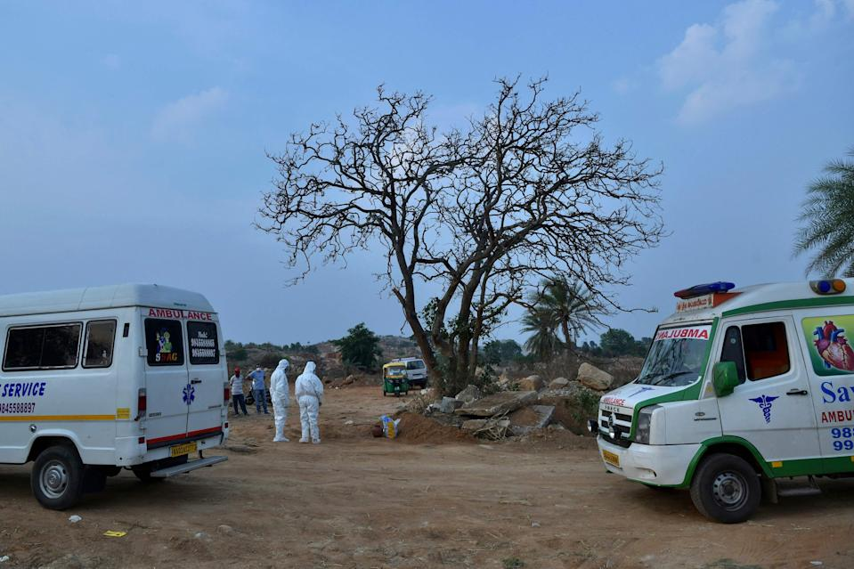 <p>Ambulances carry bodies of people who died of Covid-19, at an open-air crematorium in Karnataka on 1 May 2021</p> (AFP via Getty Images)