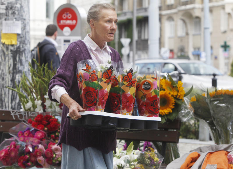 In this Sept. 5, 2013 photo, a florist carries flowers in trendy Savior Square in Warsaw, Poland. It has become one of the capital city's trendiest places after political and economic reform and attracts tourists, students and professionals with its numerous cafes and leisurely ambiance. (AP Photo/Czarek Sokolowski)
