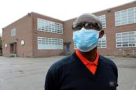 Apollinaire Nduwimana poses outside a school near his lodging in Toronto
