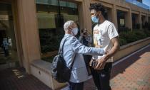 North Carolina basketball player Leaky Black greets head coach Roy Williams at the Dean Smith Center on campus prior to an NCAA college basketball news conference, Thursday, April 1, 2021, in Chapel Hill, N.C. Williams announced his retirement. (Travis Long/The News & Observer via AP)