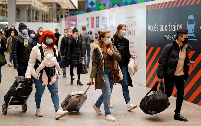 Passengers wearing protective face masks walk to board a train at Paris's Montparnasse railway station to go to the provinces to avoid the third lockdown imposed in the capital. - Chesnot