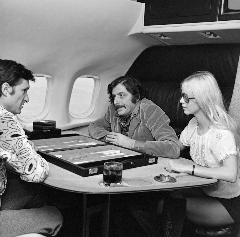 <p>Hugh Hefner (left) enjoys a game of backgammon aboard the Playboy jet in 1971.</p>