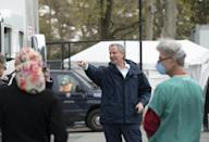 New York City Mayor Bill De Blasio (C) speaks to health workers before visiting a temporary hospital located at the USTA Billie Jean King National Tennis Center during the novel coronavirus outbreak that causes COVID-19, in the Queens borough, on April 10, 2019 in New York City