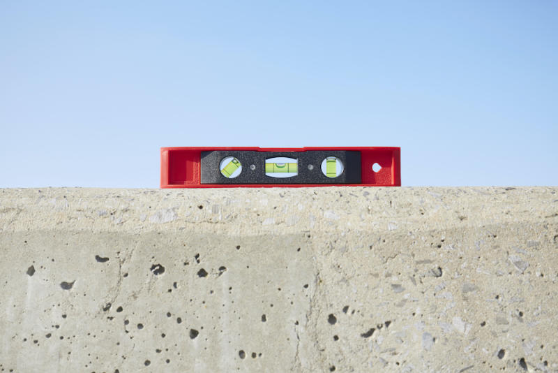 Still life of red spirit level on concrete wall against blue sky