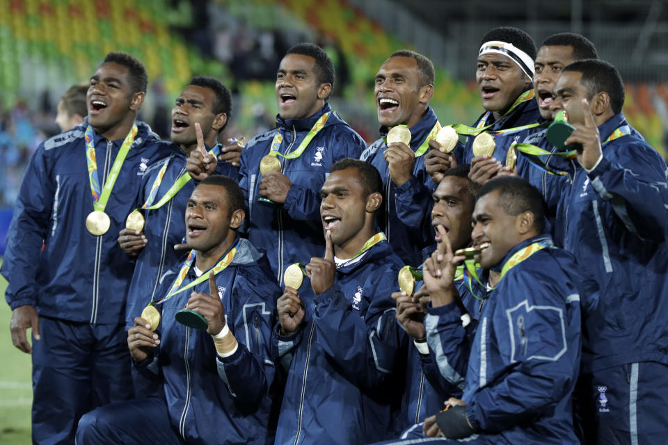 FILE - In this Aug. 11, 2016, file photo, Fiji rugby players show off their gold medal after defeating Britain in the gold medal mens rugby sevens match against Britain at the 2016 Summer Olympics in Rio de Janeiro, Brazil. It was rugby in fast forward and it generated millions of new fans across the world. Rugby sevens made its Olympic debut in Rio de Janeiro in 2016 bringing all the usual hard-hitting tackles, collisions and swerving runs but leaving out the slow-mo elements of the traditional 15-a-side game. (AP Photo/Robert F. Bukaty, File)