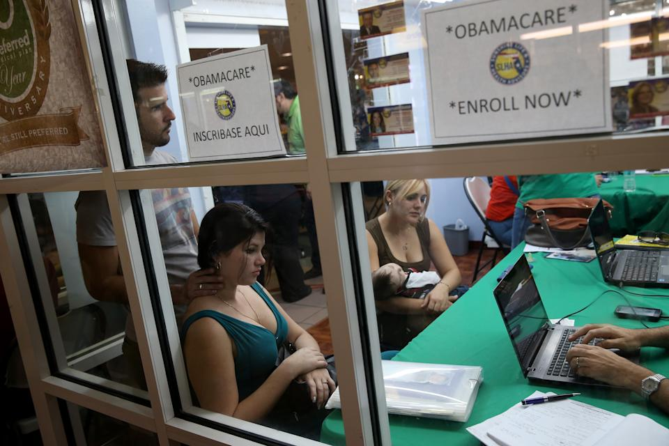 Ronnie Cabrera, Dailem Delombard and Maylin Lezcano holding Lucas Cabrera sit with an insurance agent as they try to purchase health insurance under the Affordable Care Act. (Photo: Joe Raedle/Getty Images)
