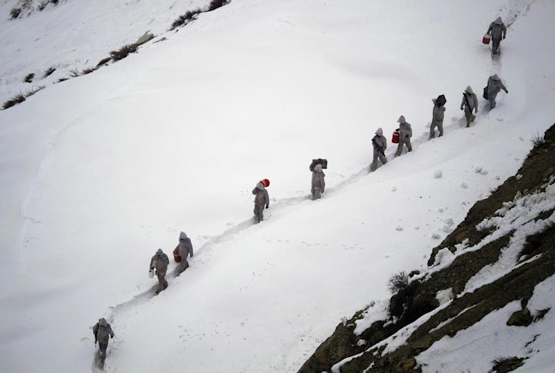 FILE - In this Feb. 19, 2012 file photo, Pakistani Army soldiers with the 20th Lancers Armored Regiment, carry supplies up the 2,400 meter (8,000-foot) mountain near their outpost, Kalpani Base, in Pakistan's Dir district. An avalanche smashed into a Pakistani army base on a Himalayan glacier close to India on Saturday, April 7, 2012, burying around 130 soldiers. (AP Photo/Anja Niedringhaus, File)