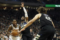 Denver Nuggets' Will Barton, left, drives to the basket against Milwaukee Bucks' Wesley Matthews, middle, and Robin Lopez (42) during the first half of an NBA basketball game Friday, Jan. 31, 2020, in Milwaukee. (AP Photo/Aaron Gash)